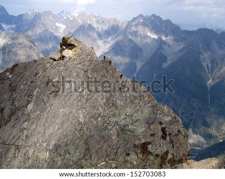 Team of climbers climbing sharp mountian range tied with rope - stock photo