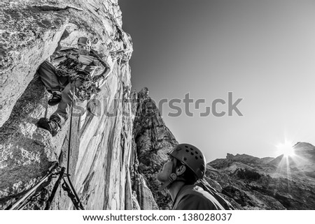 Team of climbers struggle up a steep and challenging rock spire. - stock photo