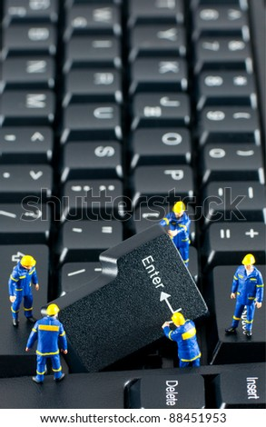 Team of construction workers working with ENTER button on a computer keyboard - stock photo