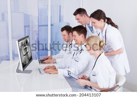 Team of dentists examining jaw Xray on computer in hospital - stock photo
