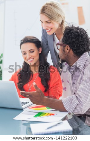 Team of designers working on laptop in bright office - stock photo
