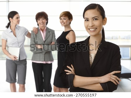 Team of diverse businesswomen, happy asian woman at front. - stock photo