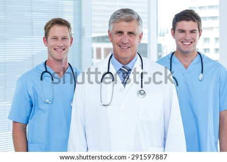 Team of doctors smiling at camera in the hospital - stock photo