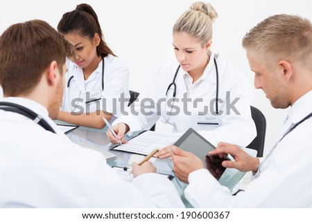 Team of doctors working at desk in clinic - stock photo