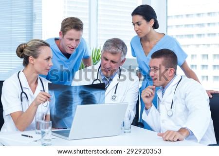 Team of doctors working on laptop and analyzing xray in medical office - stock photo