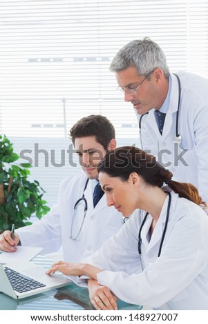 Team of doctors working together and watching something on their laptop in medical office - stock photo