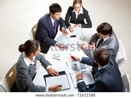 Team of five business people discussing an important question at briefing - stock photo