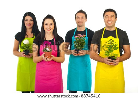 Team of four gardeners workers in colorful aprons offering flowers pots isolated on white background - stock photo