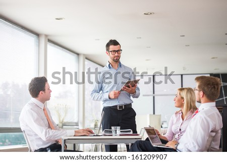 Team of four people meeting in office - stock photo