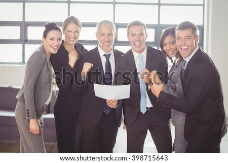 Team of happy businesspeople with certificate in the office - stock photo