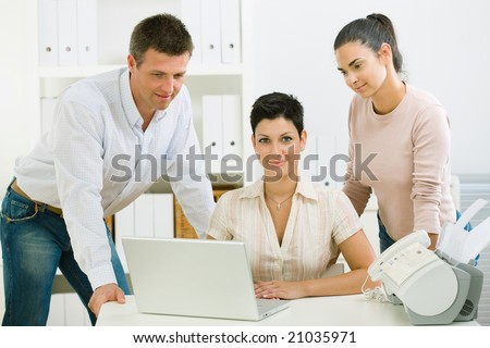 Team of happy office people working on laptop computer. - stock photo
