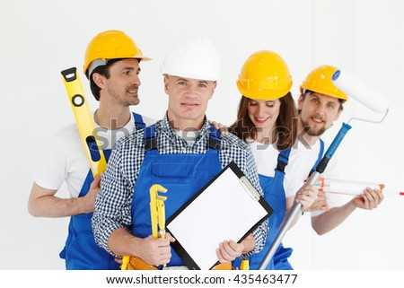 Team of happy workers with tools ready to work - stock photo