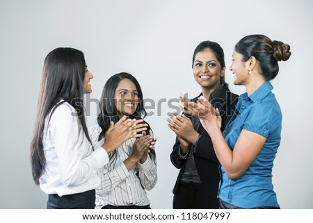 Team of Indian business women applauding good news - stock photo