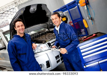 Team of mechanics working on a car at the garage - stock photo