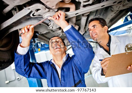 Team of mechanics working under a car at the garage - stock photo