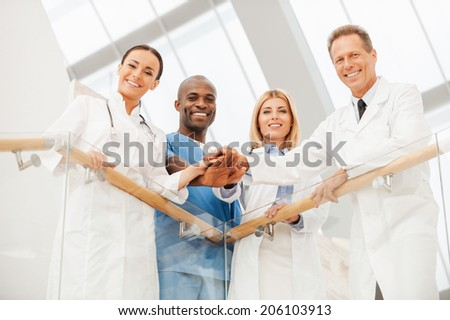 Team of medical experts. Low angle view of four happy medical doctors standing close to each other and holding their hands together while leaning at the handrail - stock photo
