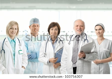Team of medical professionals looking at camera, smiling in hospital lobby. - stock photo