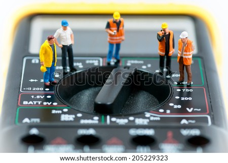 Team of miniature workers on top of multimeter. Macro photo - stock photo
