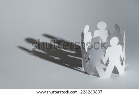 Team of paper doll people holding hands, isolated on white. Concept of friendship and support - stock photo