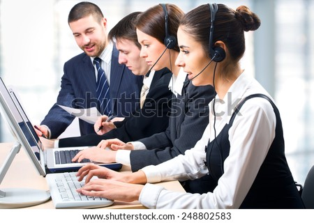 Team of people working with headsets on in a call center   - stock photo