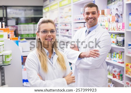 Team of pharmacists smiling at camera at the hospital pharmacy - stock photo