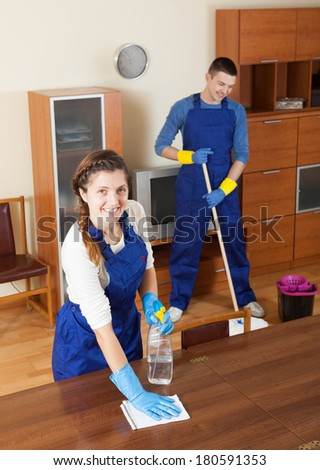 Team of professional cleaners cleaning in living room - stock photo