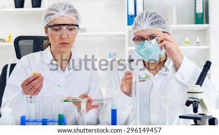 Team of scientists in a laboratory working on chemical testing. - stock photo