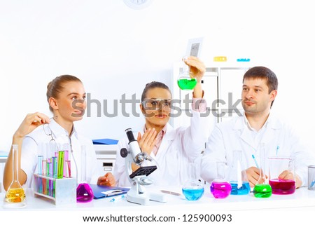 Team of scientists working with liquids in laboratory - stock photo
