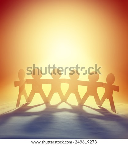 Team of six paper-chain people holding hands in front of bright sky   - stock photo
