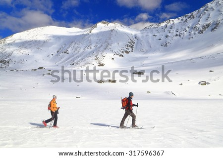 Team of ski mountaineers traversing a snow covered valley in winter - stock photo