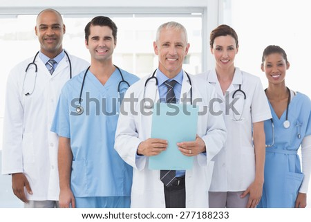 Team of smiling doctors looking at camera in medical office - stock photo