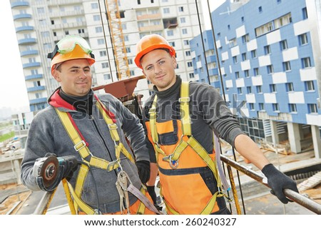 Team of smiling facade builders workers in protective uniform at construction building site - stock photo