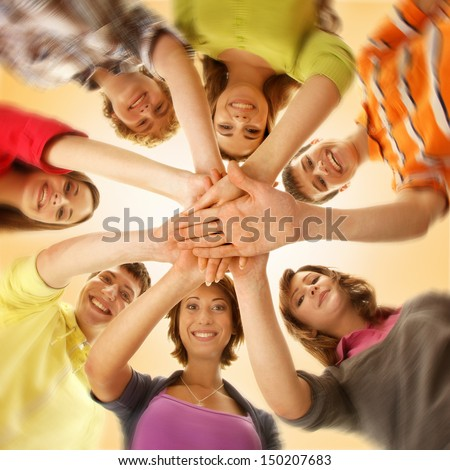 Team of smiling teens staying together and looking at camera  - stock photo
