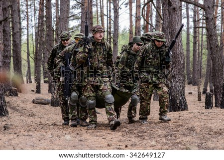 Team of soldiers evacuate soldier on stretcher - stock photo