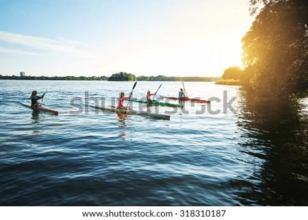 Team of sports kayaks racing on the lake - stock photo