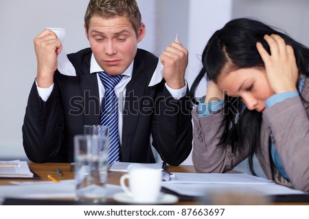Team of 2 stressed and depressed business people sitting at conference table, negotiation failure or bankruptcy concept - stock photo