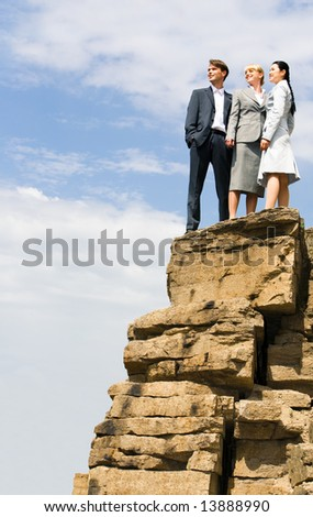 Team of successful businesspeople stand together on the mountain - stock photo