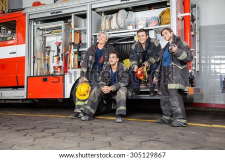 Team of thoughtful firefighters looking away by firetruck at station - stock photo