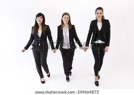 Team of three business women holding each other by hands. Caucasian and Chinese business women wearing office suits. Isolated on white background. - stock photo