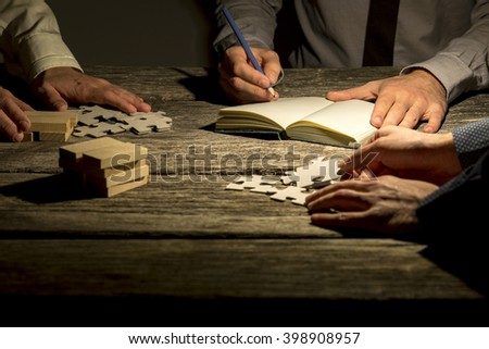 Team of three businessmen working on a project or assignment late at night with one making notes and the other two arranging puzzle pieces and wooden pegs on textured wooden desk. - stock photo