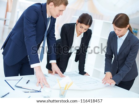 Team of three engineers discussing blueprint at meeting - stock photo