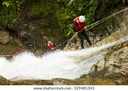Team Of Two Young Women Wearing Waterproof Equipment Descending A Waterfall - stock photo