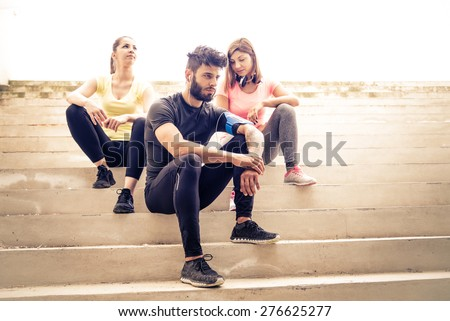 Team of urban runners getting ready for training - Muscled man and sportive women with sportwear sitting on stairs  - Friends working out to keep fit and healthy - stock photo