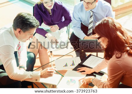 Team of women and men working in office discussing documents - stock photo