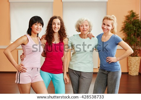 Team of women at fitness studio with senior lady - stock photo