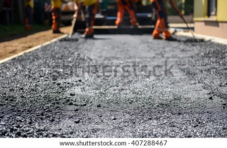Team of Workers making and constructing asphalt road construction with finisher. The top layer of asphalt road on a private residence house driveway - stock photo