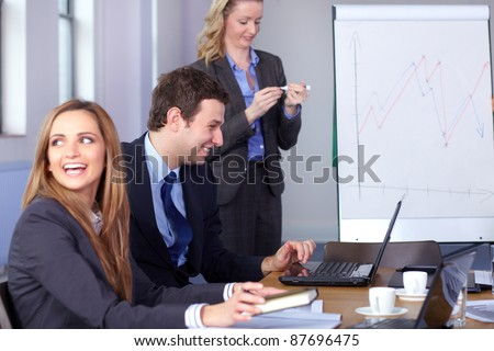 Team of 3 young business people during meeting, two of them sitting at conference table while one woman just finish her presentation - stock photo