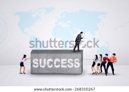 Team of young entrepreneurs try to move a stone with a text of success - stock photo