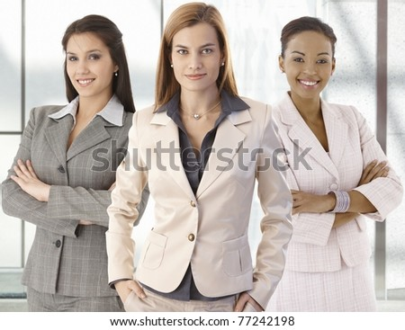 Team portrait of happy businesswomen standing on office corridor, looking at camera, smiling.? - stock photo