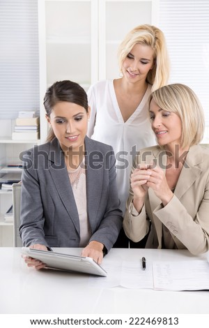 Team: Successful business team of woman in the office talking together looking at tablet computer. - stock photo